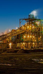 A mining factory illuminating the area at dusk