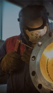 Man wearing protective equipment welding